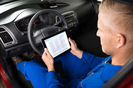 car mechanic: Mechanic Sitting In Car Looking At Graph On Digital Tablet