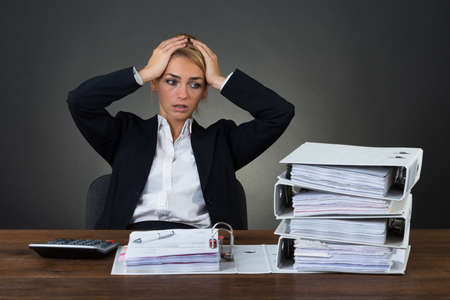 bank records: Tired businesswoman with hands on head sitting at desk over gray background