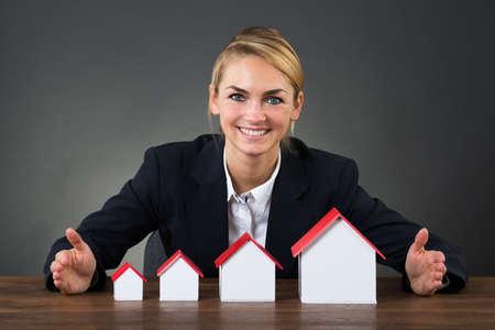 incremento: Retrato de mujer de negocios feliz con modelos de casas dispuestas en orden gráfico