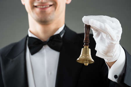 hospitality staff: Midsection of waiter holding ring bell against gray background