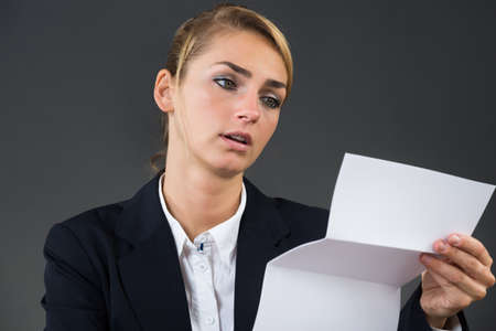 person reading: Shocked young businesswoman reading letter at desk over gray background Stock Photo