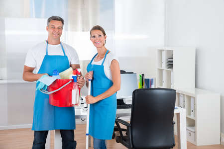 cleaning services: Two Happy Cleaners With Cleaning Equipments In Office