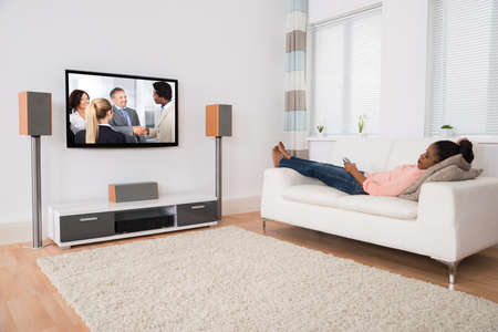 relajado: Mujer africana joven caer dormido mientras ve la televisi�n en el hogar Foto de archivo