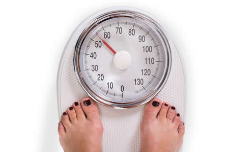 high scale: High angle view of womans legs on weighing scale over white background