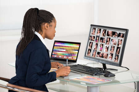 Young African Designer Retouching Photos On Computer