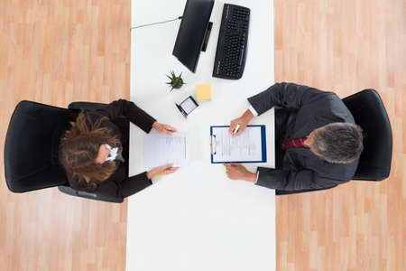 High Angle View Of Mature Businessman Interviewing Female Candidate For Job Foto de archivo
