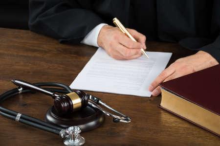 Buik van rechter schrijven op juridische documenten met houten hamer en stethoscoop aan de balie in rechtszaal