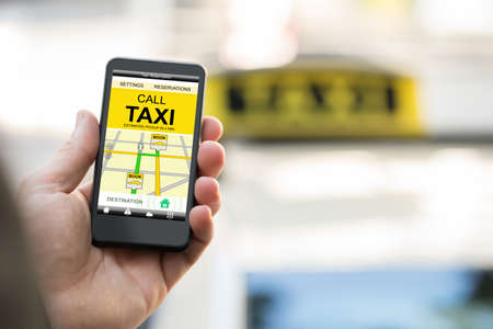 taxi sign: Close-up Of Person Booking Taxi On Smart Phone Stock Photo