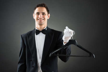 hospitality staff: Portrait of happy male housekeeper holding hanger while standing against gray background