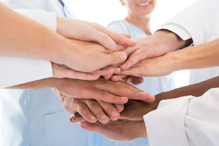 trabajo en equipo: Imagen recortada de equipo médico de apilamiento manos contra el fondo blanco