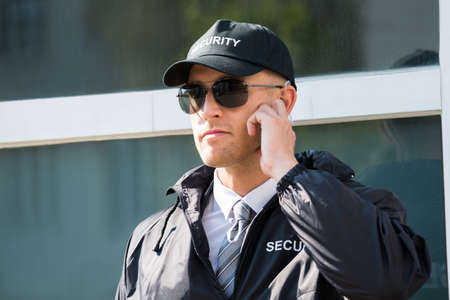 security uniform: Close-up Of Security Guard Standing In Front Of The Entrance Listening To Earpiece Stock Photo