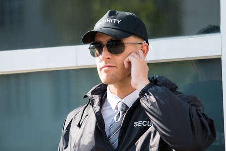 seguridad en el trabajo: Primer De La Guardia de seguridad se coloca delante de la entrada escuchando el auricular Foto de archivo