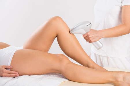 piernas: Sección media de esteticista femenina que usa la máquina de láser en la pierna de cliente en el salón Foto de archivo