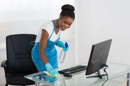 personal de limpieza: Sonriendo limpieza de la mujer africana joven turística con un trapo Foto de archivo