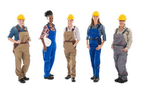 Full length portrait of multi ethnic female carpenters standing in row against white background