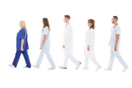 Full length side view of medical professionals walking in row against white background Imagens