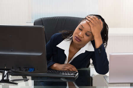 Young Depressed Businesswoman Sitting At Office Desk Stock Photo