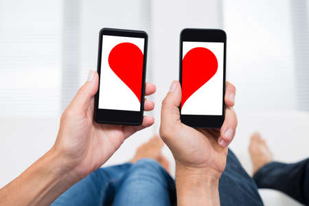 Close-up Of Two People Hands With Mobile Phones Showing Two Halves Of Heart Shape