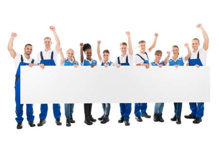 large woman: Full length portrait of happy janitors with arms raised holding blank billboard against white background