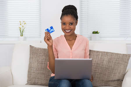 african women: Happy African Woman Using Debit Card For Shopping Online On Laptop