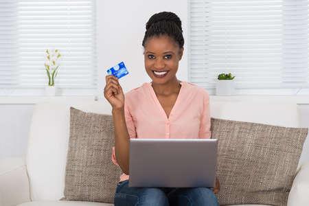 mujeres africanas: Mujer africana feliz que usa la tarjeta de débito para compras en línea en la computadora portátil