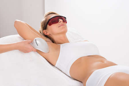 hair: Young woman having underarm laser hair removal treatment in salon Stock Photo
