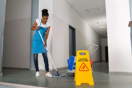 mopping: African Woman Mopping Corridor Besides Caution Sign