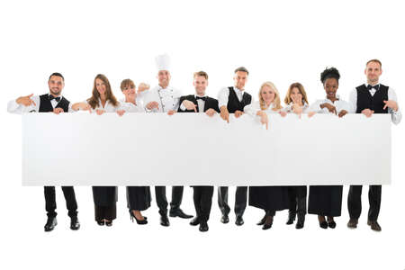 hospitality industry: Portrait of confident restaurant staff holding blank billboard against white background Stock Photo