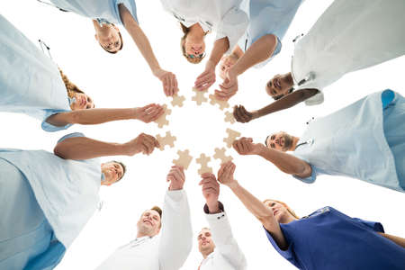 Directly below shot of medical team joining jigsaw pieces in huddle against white background Stockfoto
