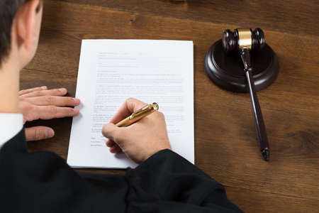 hand writing: High angle view of male judge writing on legal documents at desk in courtroom