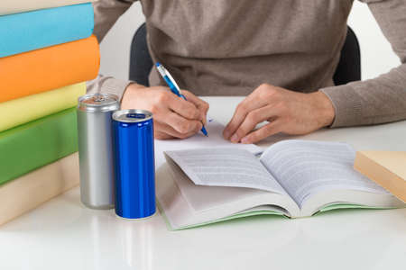 energy drink: Midsection of male student writing in book while studying at table