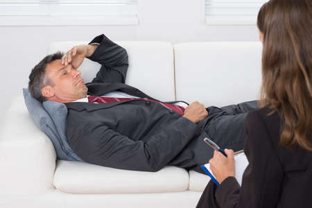 psychologist: Patient Relaxing On Couch In Front Of A Female Psychiatrist With Clipboard Stock Photo