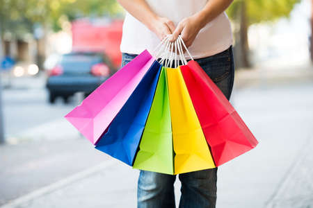 midsection: Midsection of young woman holding colorful shopping bags