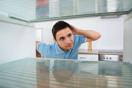 refrigerator: Shocked young man looking into empty refrigerator at home