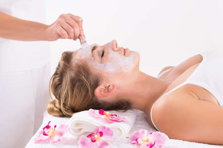 exfoliate: Cropped image of beautician applying mask on customers face at salon Stock Photo