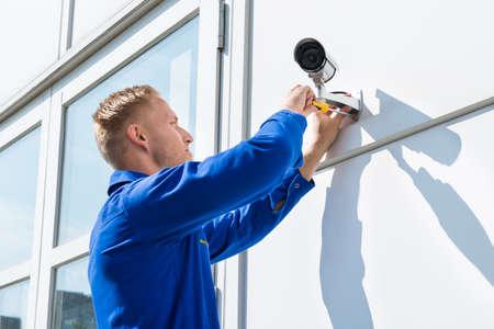 Technician Fixing Camera On Wall With Screwdriver Foto de archivo