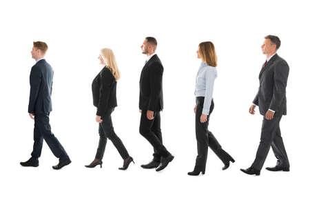caminando: vista lateral integral de los hombres de negocios a pie contra el fondo blanco Foto de archivo