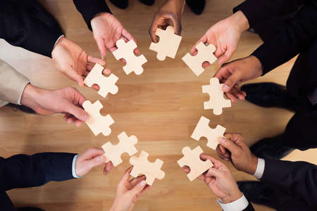 Directly above shot of business people joining jigsaw puzzle pieces in office 스톡 콘텐츠