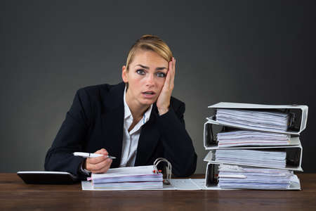 bank records: Stressed businesswoman looking at folders while working at desk over gray background Stock Photo