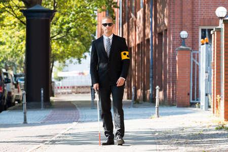 1 man: Blind Man Walking On Sidewalk Holding Stick Wearing Armband