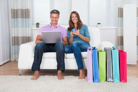 buy: Happy Mature Couple Sitting On Sofa Shopping Online With Laptop And Credit Card