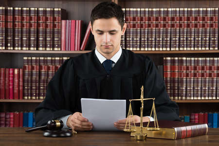 sentence: Male judge reading documents while sitting at desk in courtroom Stock Photo