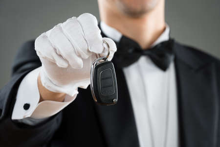 midsection: Midsection of waiter holding car key against gray background Stock Photo