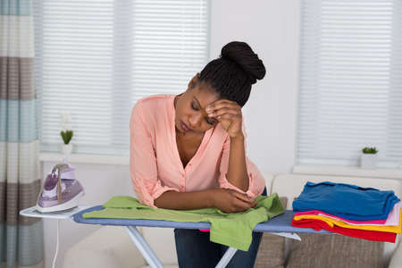 iron curtains: Young African Woman Exhausted While Ironing Clothes At Home Stock Photo