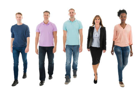Full length portrait of creative business people walking with manager against white background