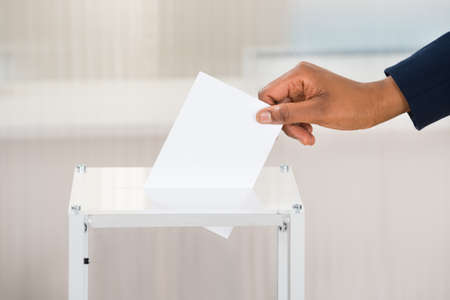 ballot papers: Close-up Of A Persons Hand Putting Ballot In Box