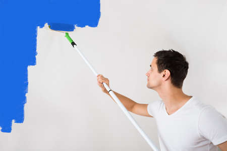man painting: Young man painting wall with blue paint roller at home