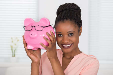 woman holding money: Close-up Of Smiling Young African Woman Holding Piggybank
