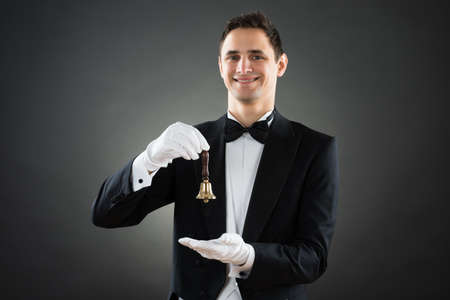 hospitality staff: Portrait of happy young waiter holding ring bell against gray background