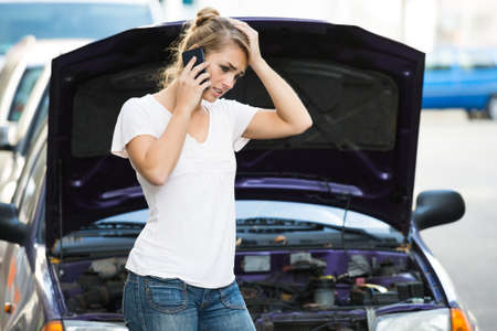 car: Young woman using mobile phone while looking at broken down car on street
